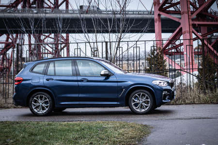 Moscow. Russia - December 06, 2019: The all-new BMW X3. Blue crossover stands on the street at night. Premium German SUV. Side view