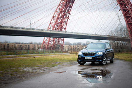Moscow. Russia - December 06, 2019: The all-new BMW X3. Blue crossover stands on the street at night. Premium German SUV. front view
