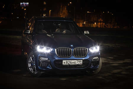 Moscow. Russia - December 06, 2019: The all-new BMW X3. Blue crossover stands on the street at night. Premium German SUV front view.