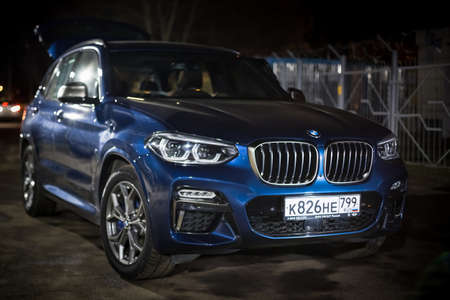 Moscow. Russia - December 06, 2019: The all-new BMW X3. Blue crossover stands on the street at night. Premium German SUV. Parked