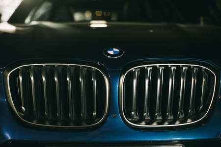 Moscow. Russia - December 06, 2019: Close up of frontal part, headlights and frill The all-new BMW X3. Blue crossover stands on the street at night. Premium German SUV.