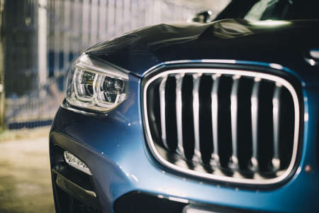 Moscow. Russia - December 06, 2019: The all-new BMW X3. Blue crossover stands on the street at night. Premium German SUV. front grill and headlights of premium car