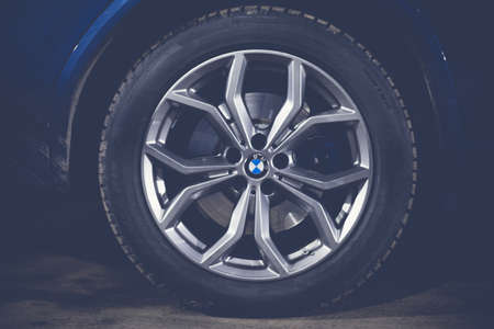 Moscow. Russia - December 06, 2019: The all-new BMW X3. Blue crossover stands on the street at night. Premium German SUV. Wheels close up, matte image