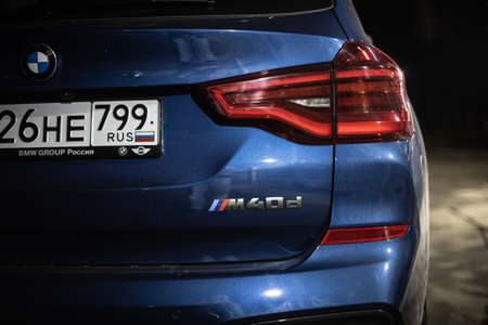 Moscow. Russia - December 06, 2019: The all-new BMW X3. Blue crossover stands on the street at night. Premium German SUV. Back side and taillights M40d engine