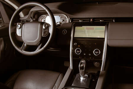 Luxury car inside, automatic gear stick of a modern car. Dark leather interior brown toned image