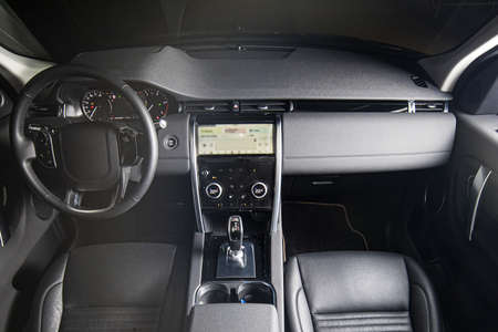 Interior of luxury suv car with black leather steering wheel and automatic shift gear. 