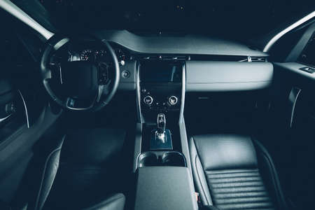 Luxury car inside, automatic gear stick of a modern car. Dark leather interior. matte green toned