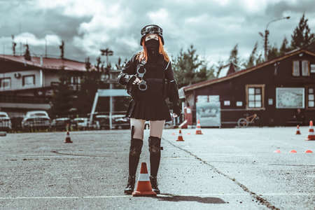A girl in black military uniform of a special forces detachment. Without identification marks. Looks at the camera. A woman is wearing a protective mask. She stands in the background of the house and parking. Standard-Bild