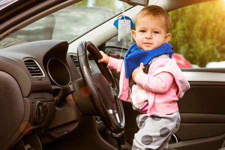 Happy Little kid in a car. Stands in the driver's seat and holds the wheel. The car door is open. Infant driving. Baby looks thoughtfully out of the car.