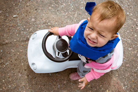 A small child is riding a toy car. and very unhappy. View from above. A special car that needs to be kicked. Tolokar.