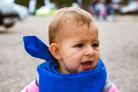 A small child with a blue bandana bandage around his neck. The kid screams to the side and calls someone.