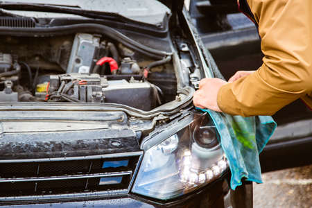 A man changes his headlights. Replacing the headlight lamps, the hood is open. Car service and cleaning the engine compartment.