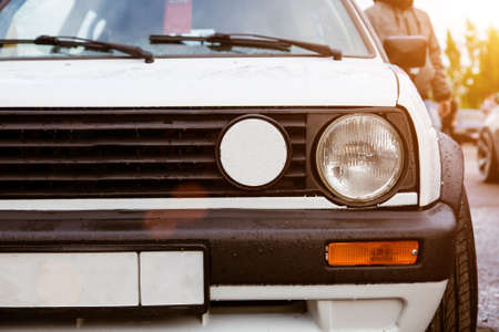 Radiator grill and headlights of an old retro car. White vintage car, close-up