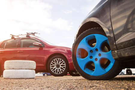 Tire service. Two cars with alloy wheels. Blue wheels. Outdoors. Standard-Bild