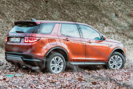 Moscow, Russia - December 20, 2019: Back side View of all new premium england suv. Land rover Discovery sport parked in the forest. Orange all wheel drive car standed on the ground.