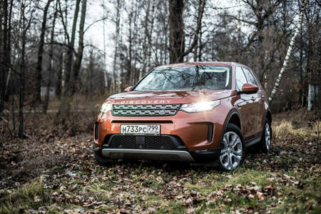 Moscow, Russia - December 20, 2019: Front side View of all new premium england suv. Land rover Discovery sport parked in the gray forest. Orange all wheel drive car standed on the ground.