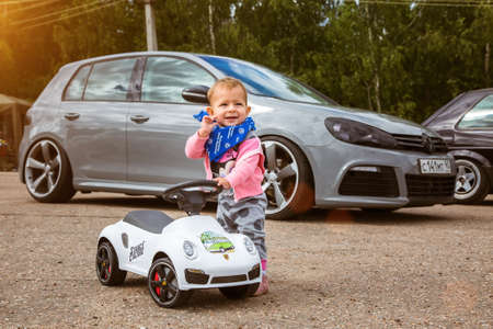 Moscow, Russia - July 06, 2019: A small child is standing with a Porsche toy car on the background of a real car. Tuned Volkswagen Golf gray color on background. The kid dreams of a real car. Editorial