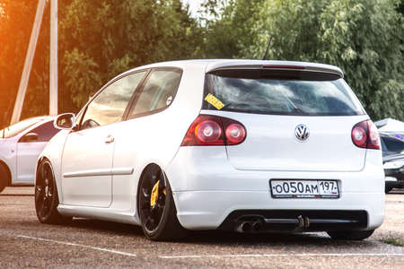 Moscow, Russia - July 06, 2019: White tuned Volkswagen Golf MK5. The back of the car with lowered suspension. and black rims. GTI version. Washed wheels. A rag is hanging on the wheel.