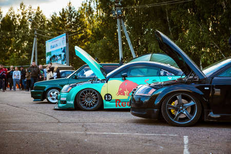 Moscow, Russia - July 06, 2019: Two tuned Audi TTs. One wrapped with a special turquoise vinyl film. The car is sponsored by red bull racing. Parked on the street.