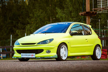 Moscow, Russia - July 06, 2019: Bright green, Peugeot 206 tuned with white rims and lowered suspension. It is in the parking lot. Well-groomed car drawn by a special film.