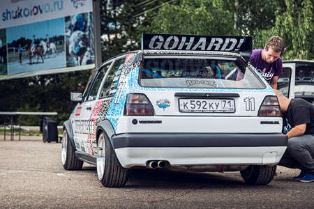 Moscow, Russia - July 06, 2019: White Volkswagen Golf 2 powerfully tuned for racing with a roll cage, an aerodynamic spoiler, an understated car with custom BBS wheels. Rally Editorial
