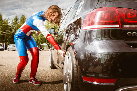 Moscow, Russia - July 06, 2020: Woman Captain America. He hits the car and a dent remains on it. Girl superhero. Costume. wonder Woman. Damaged car. cosplay, unusual outfit Editorial