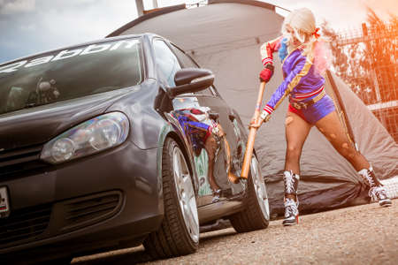 Moscow, Russia - July 06, 2020: Harley Quinn hits a parked black car with a baseball bat. There is a dent in the car, the car is damaged. Cosplay, Girl dressed as a character costume