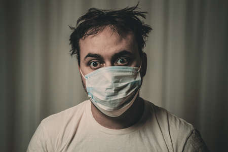 Unshaven man in a medical mask with tousled hair looking at the camera. On white background. Image toned in gloomy tones. dark, depressing.