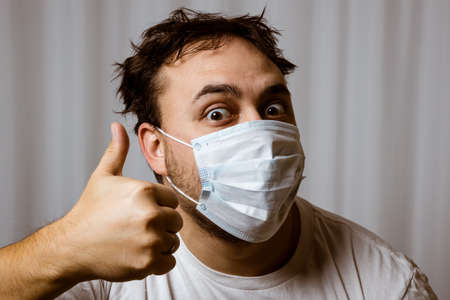 Unshaven man in a white medical mask and white t-shirt with tousled hair looks at the camera and shows a gesture - thumbs up. On white background.