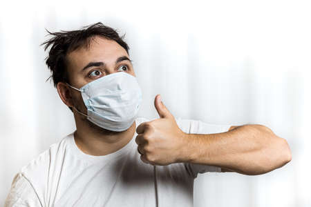 An unshaven man in a medical mask and a white T-shirt with tousled hair looks to the right and up and shows a gesture - thumbs up. On white background. Standard-Bild