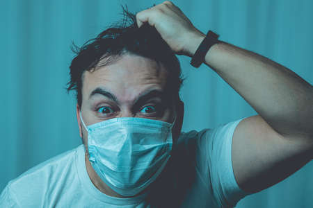 An unshaven man in a medical mask and a white T-shirt with disheveled hair tears his hair. Depression and insanity in isolation. The image is toned with a blue tint.