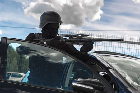 Masked soldier in a mask without stripes and identification marks. Military man in black protective combat gear and a gun. Aiming from cover. Standing outside the door of a black car on the street. Standard-Bild