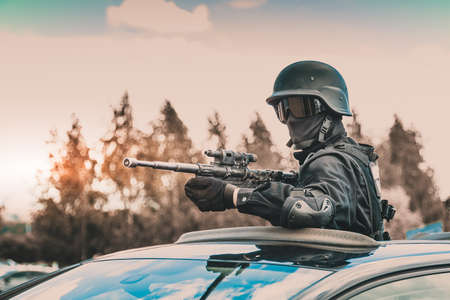 Masked soldier in a mask without stripes and identification marks. Military man in black protective combat gear and a gun. Aiming from cover. It fires from the sunroof of a black car. Standard-Bild