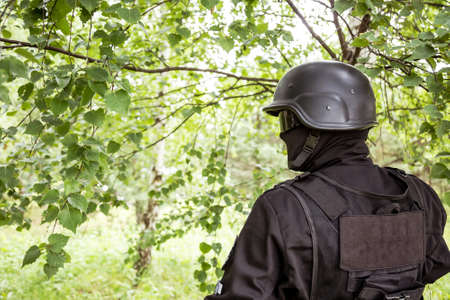 A soldier in special black equipment. Warrior without insignia and stripes. Special forces in the woods aiming with weapons. Tactical exercises.