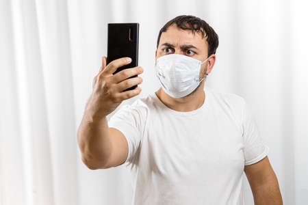 The man saw the bad news on his phone. Virus pandemic and epidemic. A man wearing a medical mask on his face. Banco de Imagens