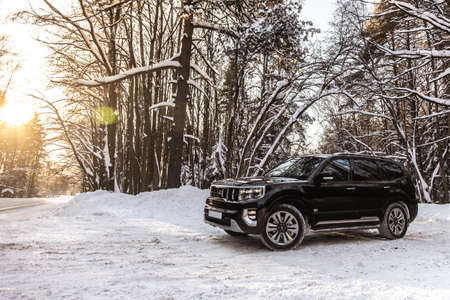 Moscow, Russia - February 15, 2021: Kia Mohave 2021 black SUV parked in the forest in winter. General shot of the car from the front. Controlled skidding in snowdrifts. Éditoriale