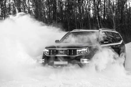 MOSCOW, RUSSIA - FEBRUARY 15, 2021: Kia Mohave 2021 black SUV drives in a controlled drift. Drift on four-wheel drive. winter, drifts. AWD offroad