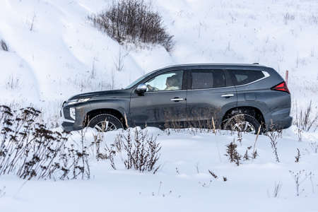 Moscow, Russia - February 17, 2021: All new Mitsubishi Pajero Sport. Facelifted suv. Side and backside view. winter, the car is driving off-road. Éditoriale