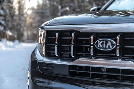 Moscow, Russia - February 15, 2021: Kia Mohave 2021 black SUV parked in the forest in winter. Close-up. LED headlights, radiator grill.
