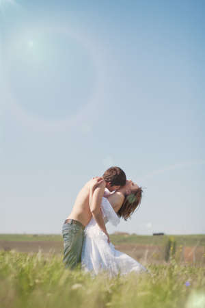 beautiful young pair kissing and hugging on green grass photo