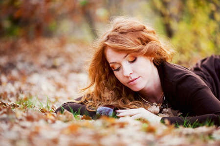 outdoor glamour: The red-haired girl in autumn leaves  outdoor shot