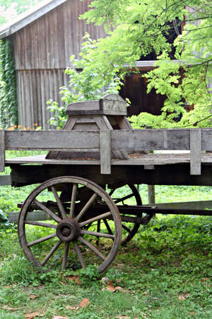 old wood farm wagon: An old weathered wagon sitting by a fence in front of an old barn. Stock Photo