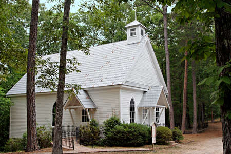 An old white wood frame country church in the woods. Archivio Fotografico