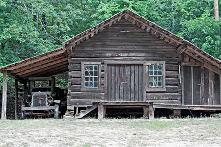 An old log cabin with an attached one car garage and a dilapidated old truck sitting in it. photo