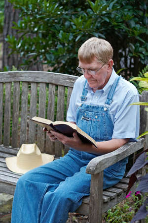 discipleship: An older man in overalls sitting outside reading the Bible. Stock Photo