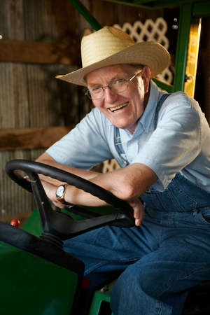 A smiling farmer sitting on his tractor in the barn. 版權商用圖片