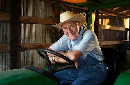 A farmer sitting on his trtactor in the barn. 版權商用圖片