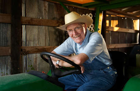 implementing: A farmer sitting on his trtactor in the barn. Stock Photo