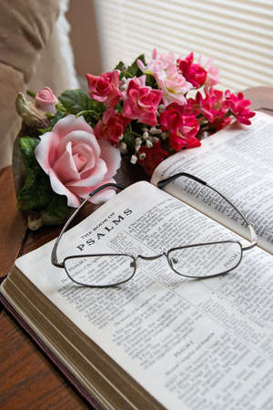 A vertical composition of an open Bible on a table with flowers and eye glasses.