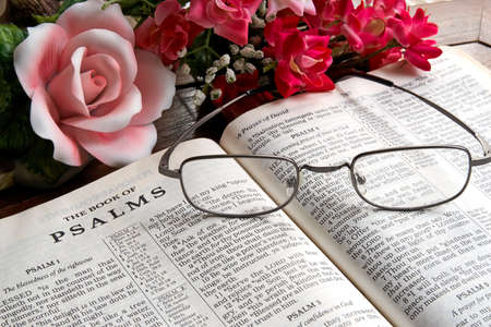 An open Bible with reading glasses lying on it and flowers in the background. Stock Photo